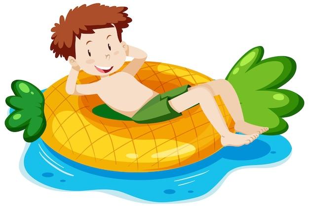 Chłopiec leżący na basenie z ananasem w wodzie na białym tle