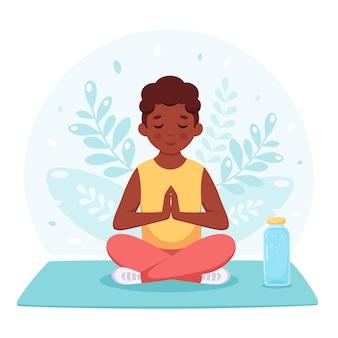Chłopiec medytujący w pozycji lotosu gimnastyczna joga i medytacja dla dzieci