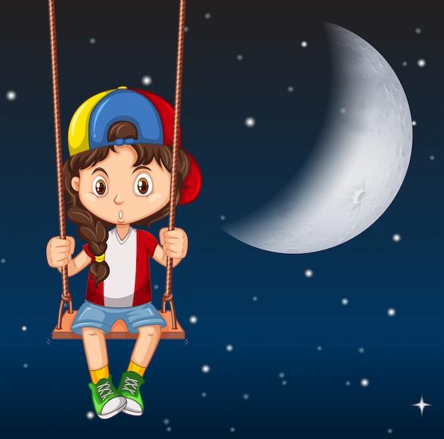 Chłopiec na huśtawce w nocy