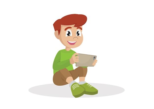 Chłopiec obsiadanie na podłoga z pastylka komputerem w rękach.