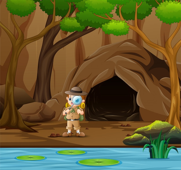 Chłopiec odkrywca stojący w pobliżu jaskini i rzeki