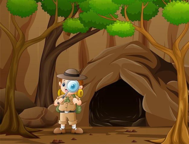 Chłopiec odkrywca stojący w pobliżu jaskini