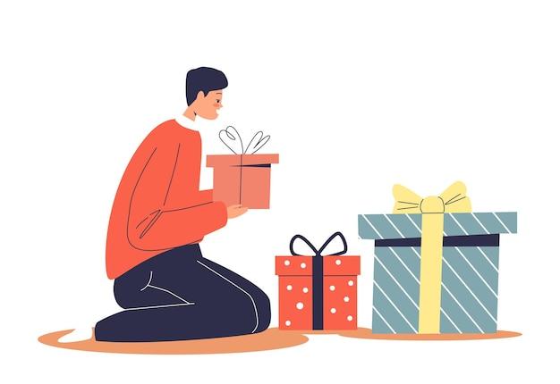 Chłopiec pakuje świąteczne prezenty w prezentowe pudełka z ozdobnym papierem przygotowując się do ferii zimowych