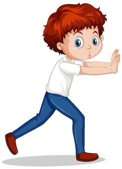 Chłopiec pchający ścianę na białym tle