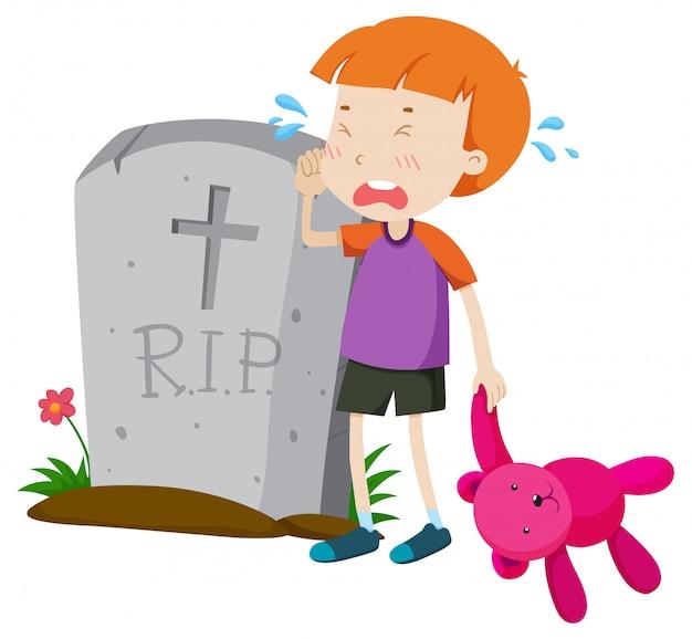 Chłopiec płacze łzami przy nagrobkiem