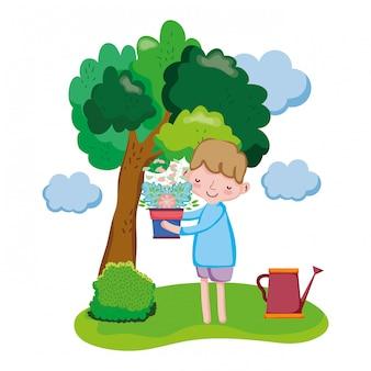 Chłopiec podnosi houseplant z kropidłem w krajobrazie