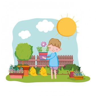 Chłopiec podnosi houseplant z ogrodzeniem i kurczątkiem