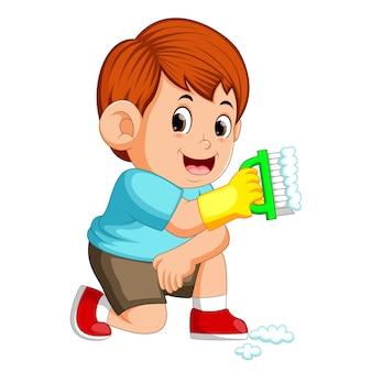 Chłopiec siedzi i trzyma zielony pędzel, aby oczyścić rzeczy