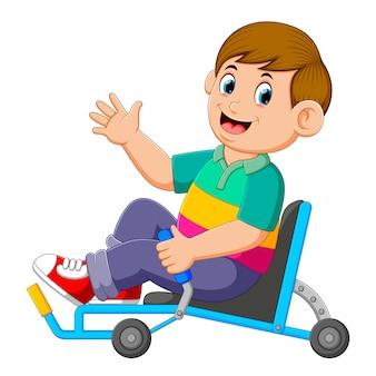 Chłopiec siedzi na leżącym trójkołowu i trzyma kontroler