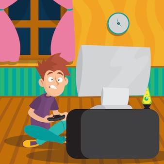 Chłopiec siedzi na podłodze i gra w gry wideo z joystickiem.