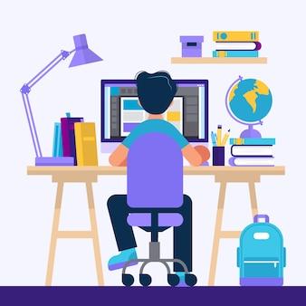 Chłopiec siedzi przy biurku, uczy się z komputerem.