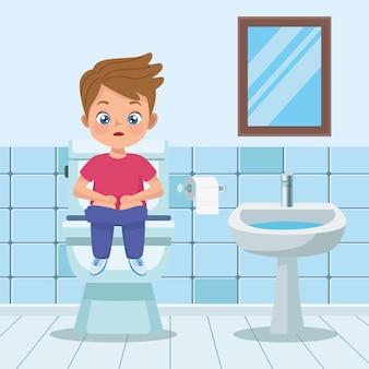 Chłopiec siedzi w toalecie