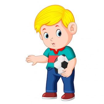 Chłopiec stoi i trzyma piłkę