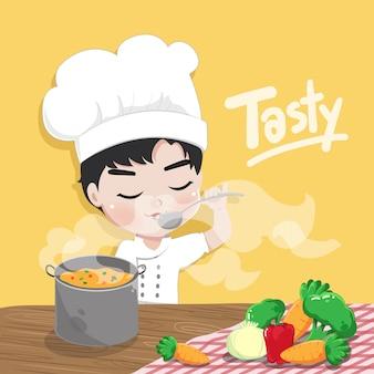 Chłopiec szef kuchni degustuje jedzenie w kuchni