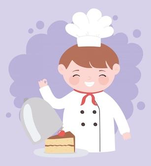 Chłopiec szefa kuchni z kawałkiem ciasta w postać z kreskówki naczynia