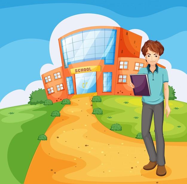 Chłopiec trzyma książkę stojącą przed budynkiem szkoły