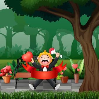 Chłopiec trzyma kwiat i serce w parku
