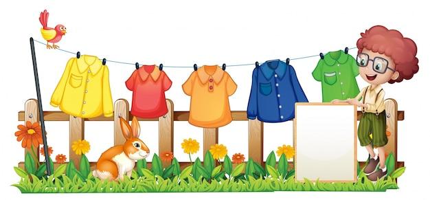 Chłopiec trzyma pustą ramę przed wiszącymi ubraniami