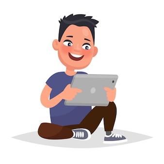Chłopiec trzyma tabletkę w rękach. ilustracja wektorowa w stylu cartoon
