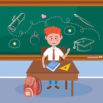 Chłopiec uczeń w biurku z książką i trójbok władcą