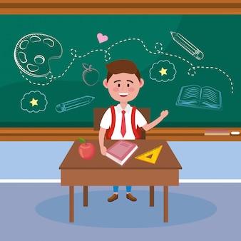 Chłopiec uczeń w biurku z książkową i jabłczaną owoc