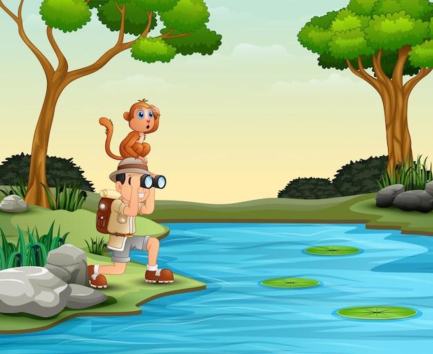 Chłopiec używa lornetki z małpą patrzeje pięknego krajobraz
