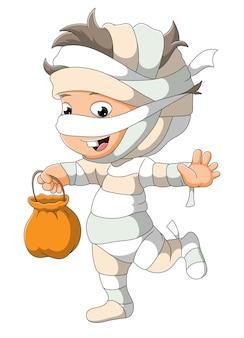 Chłopiec w kostiumie mumii trzyma kosz z tkaniny z ilustracjami