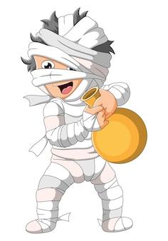 Chłopiec w kostiumie mumii trzyma złoty dzbanek z ilustracją