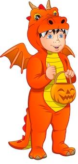 Chłopiec w stroju smoka i gospodarstwa halloween dynia