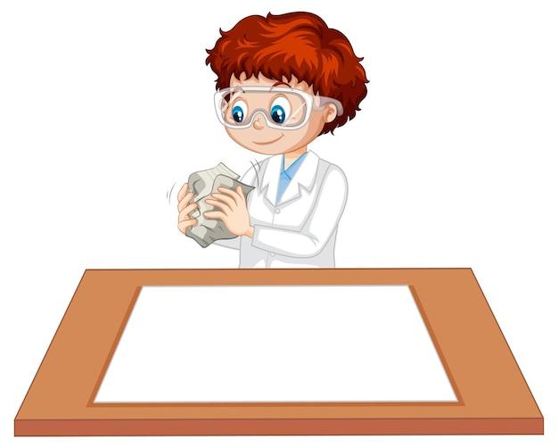 Chłopiec w sukni naukowca z pustym papierem na stole
