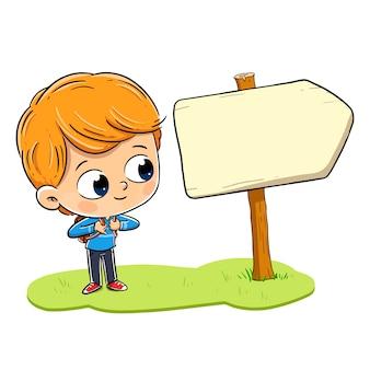 Chłopiec z plecakiem, patrząc na znak kierunku