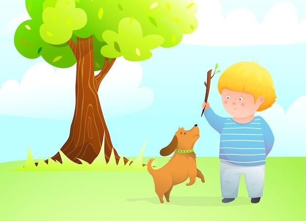 Chłopiec z przyjacielem skaczącego psa bawi się na zewnątrz, rzucając kijem dla szczeniaka na trawniku pod dębem.