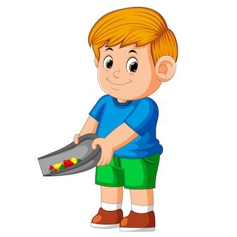 Chłopiec za pomocą niebieskiego materiału i stojącego, aby posprzątać śmieci w cieniu