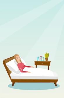 Chora kobieta z termometrem w łóżku.