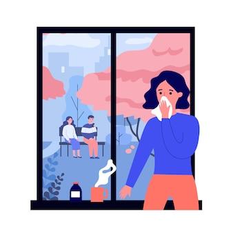 Chora młoda kobieta patrzeje okno z grypą
