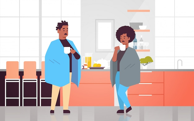 Chora para pije gorącą herbatę niezdrowy african american mężczyzna kobieta przykryta kocem cierpiący na chorobę wirusa grypy przeziębienia