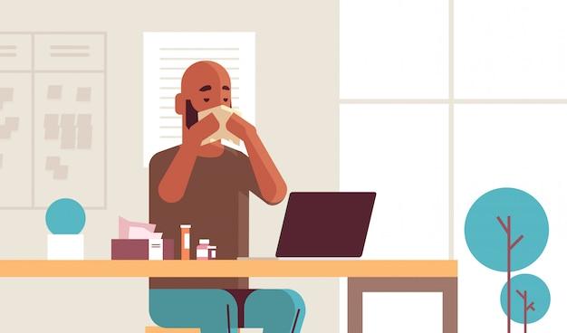 Chory biznesmen dmuchanie nosem chusteczką afroamerykanin siedzący w miejscu pracy za pomocą laptopa mężczyzna mający grypę kichanie choroba koncepcja nowoczesne wnętrze biurowe portret poziomy