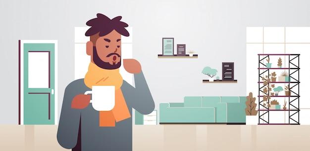 Chory mężczyzna kichający pijący gorącą herbatę niezdrowy afroamerykanin w szaliku cierpiący na przeziębienie grypy choroba wirusowa koncepcja nowoczesny salon wnętrze płaski portret poziomy