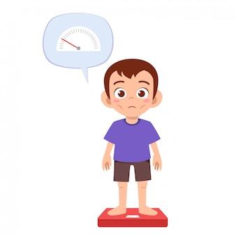 Chudy, smutny chłopiec używa wagi