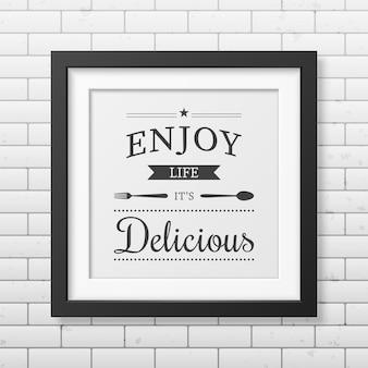 Ciesz się życiem, które jest pyszne - cytat typograficzny w realistycznej kwadratowej czarnej ramce na ścianie z cegły