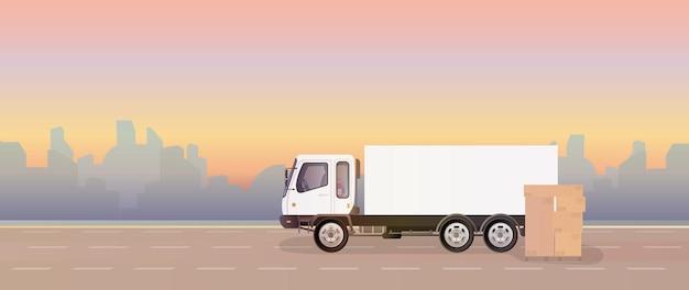 Ciężarówka i paleta z pudełkami. na drodze stoi ciężarówka. pudełka kartonowe. pojęcie dostawy i załadunku ładunku. .