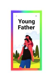 Córka siedzi na ramionach ojca szczęśliwa rodzina chodzenie na zewnątrz rodzicielstwo koncepcja ojcostwa krajobraz tło pionowe