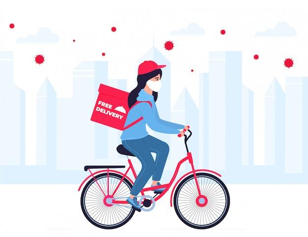 Covid-19. kwarantanna w mieście. epidemia koronawirusa. dziewczyna w masce ochronnej niesie jedzenie na rowerze. darmowa dostawa.