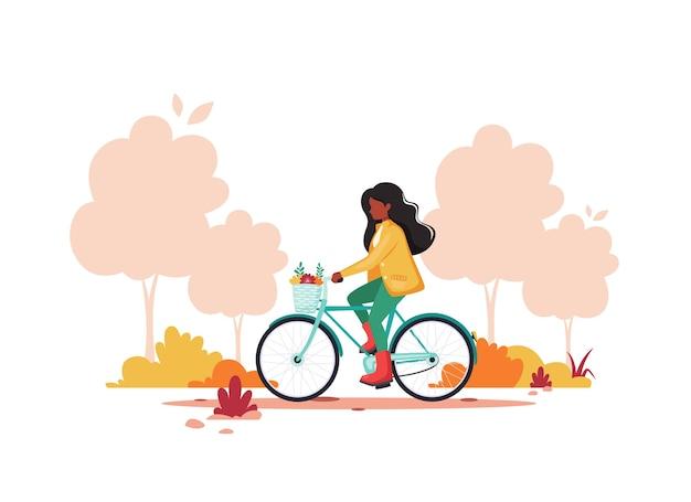 Czarna kobieta jedzie na rowerze jesienią. zdrowy styl życia, koncepcja aktywności na świeżym powietrzu.