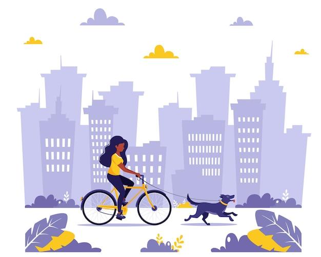 Czarna kobieta jedzie na rowerze z psem w mieście. zdrowy styl życia, koncepcja aktywności na świeżym powietrzu. w stylu płaskiej.