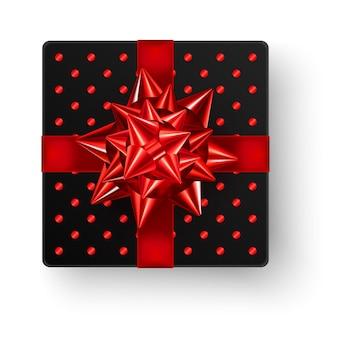 Czarne kwadratowe pudełko z dużą błyszczącą czerwoną wstążką i błyszczącym wzorem w kropki, widok z góry na białym tle.