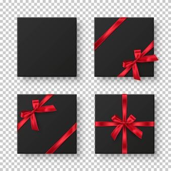 Czarne pudełka prezentowe z czerwonymi wstążkami i kokardkami.