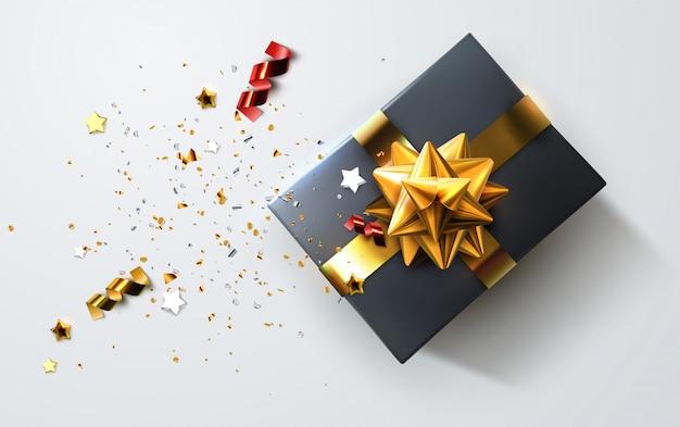 Czarne pudełko ozdobne z błyszczącymi czerwonymi wstążkami, kokardką i rozrzuconymi drobinkami konfetti i gwiazdkami. świąteczna ilustracja. widok z góry.
