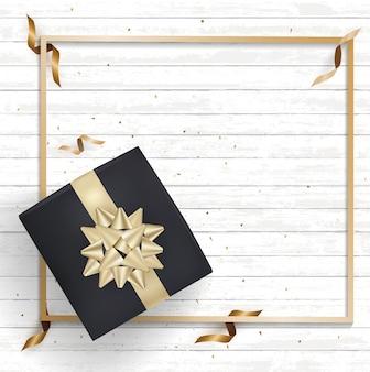 Czarne pudełko prezentowe i złote wstążki z kokardą z jasnego drewna w konfetti.