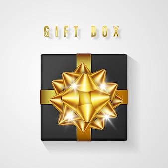 Czarne pudełko upominkowe ze złotą kokardą i widokiem z góry wstążki